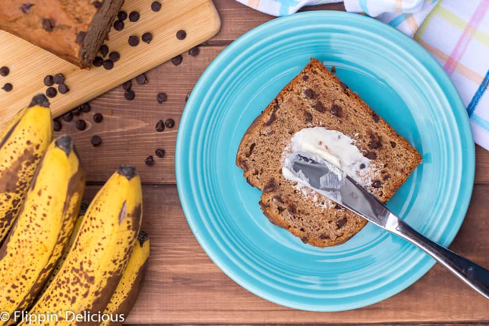 overhead view of a slice of gluten free chocolate chip banana bread on a blue plate, spread with butter.