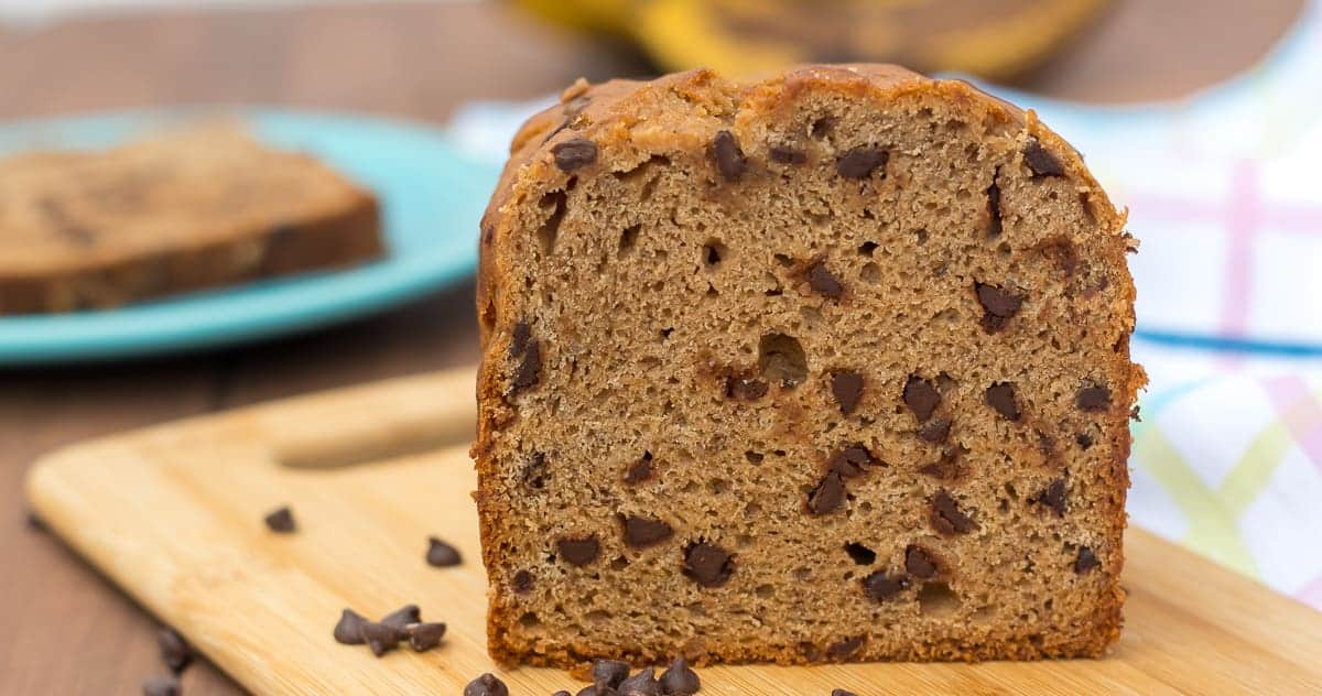 loaf of gluten free chocolate chip banana bread on a cutting board with mini chocolate chips scattered around