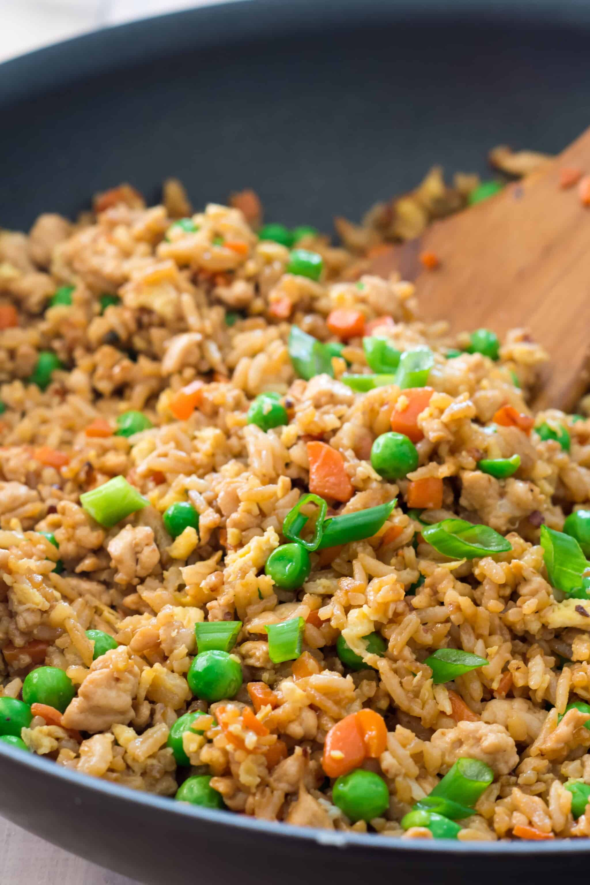 wooden spatula stirring skillet of gluten free turkey fried rice with peas, carrots, and green onions