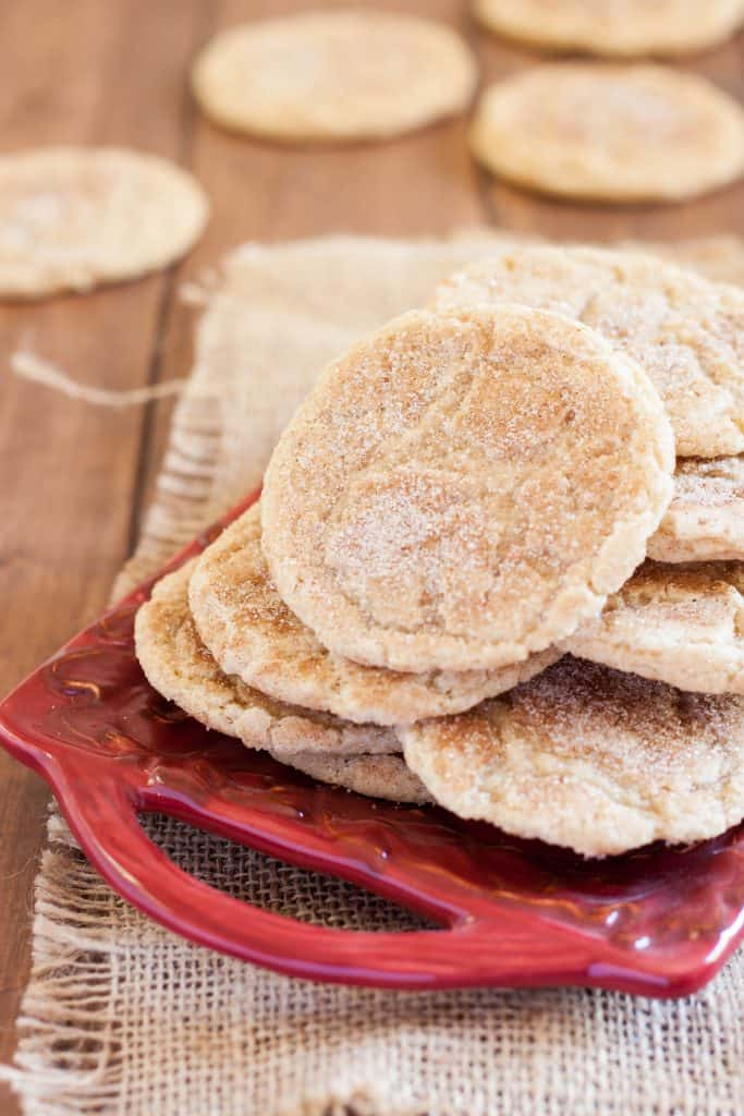 gluten free snickerdoodles on a red ceramic square plate or tray, on a wooden table with some burlap in the background