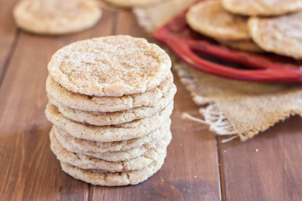 stack of gluten free snickerdoodles with cinnamon sugar on a wooden table with red tray of cookies in the bacground
