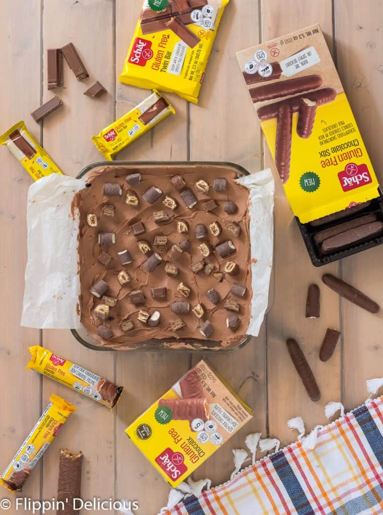 gluten free candy stuffed brownies with chocolate frosting and chopped candy bars