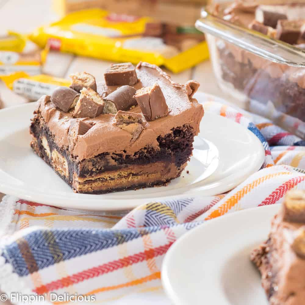 gluten free brownie stuffed with gluten free candy bars, topped with chocolate frosting on a white plate