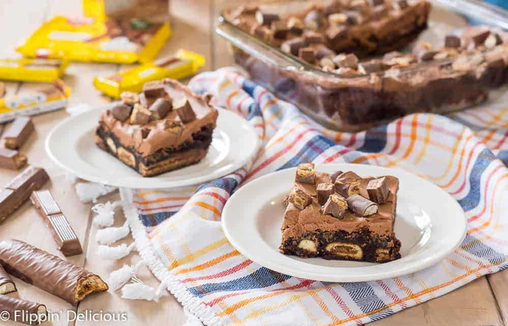 gluten free candy stuffed brownies with candy bars and chocolate frosting on a white plate