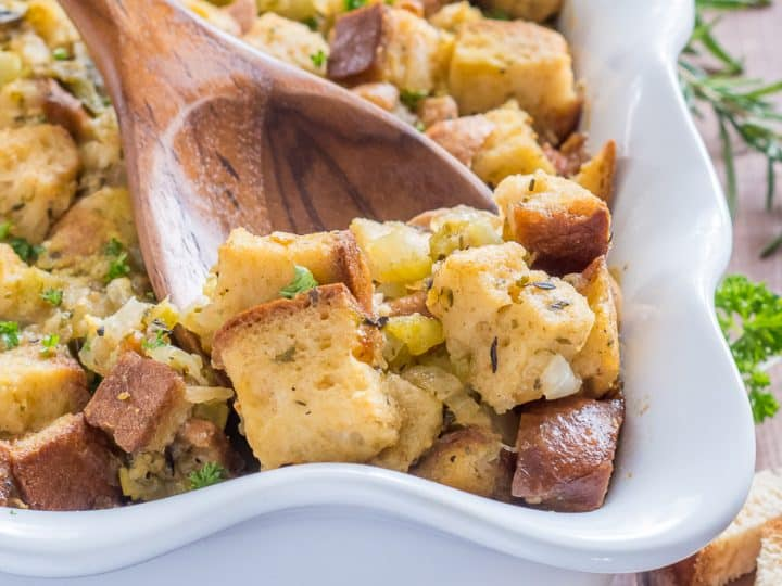 gluten free stuffing with green chile in a white casserole dish with a wooden spoon scooping out a serving