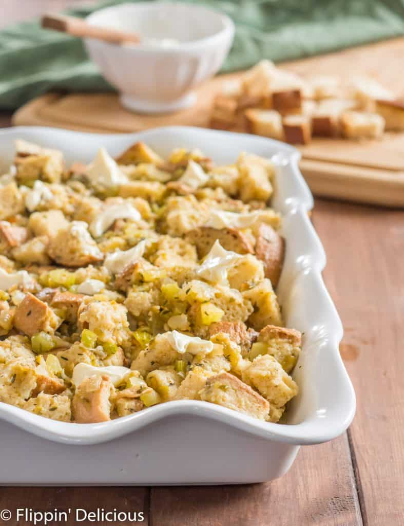 gluten free stuffing with green chile dotted with butter and ready to bake in a white casserole dish