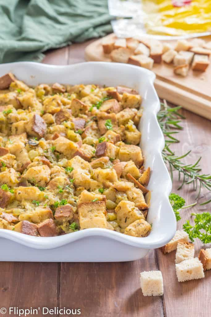 gluten free stuffing with hatch green chile in a white casserole dish on a wooden table with cubed gluten free bread and fresh herbs