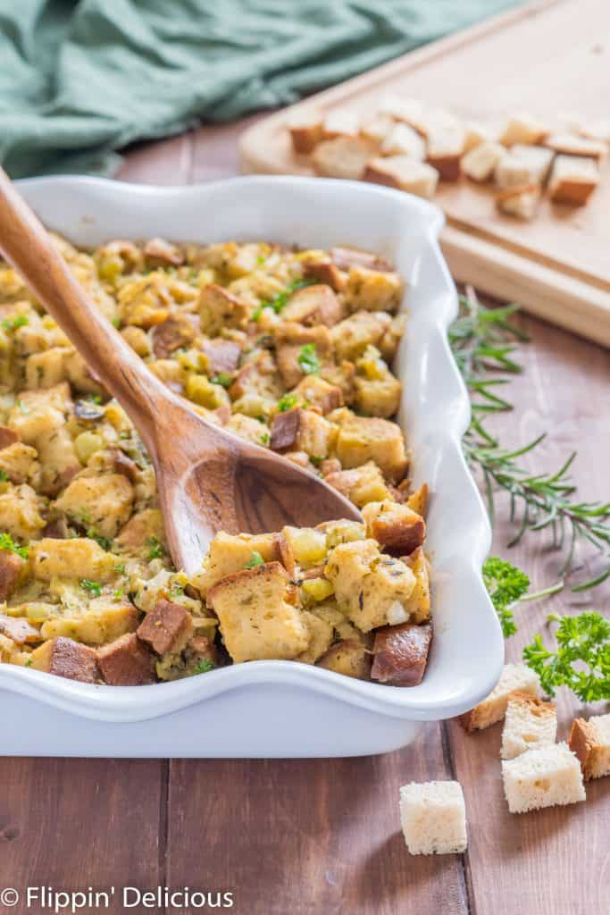 wooden spoon scooping gluten free stuffing with green chile out of a white casserole dish