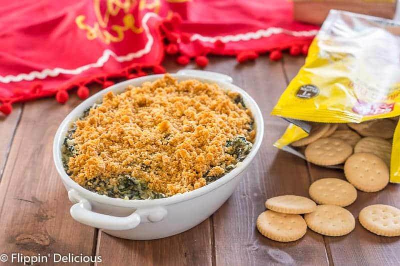 baked gluten free spinach artichoke dip beside gluten free crackers