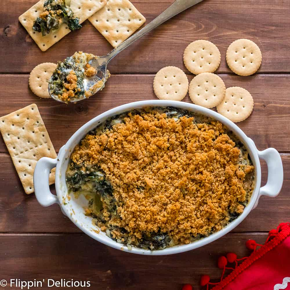 oval white dish filled with gluten free spinach artichoke dip with breadcrumbs, on a wooden table with gluten free crackers and a red tea towel