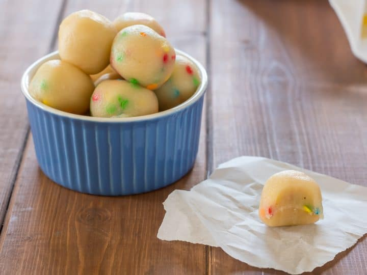 keto sugar cookie protein bites in a small blue bowl, with one protein bite on a piece of parchment paper on a wooden table