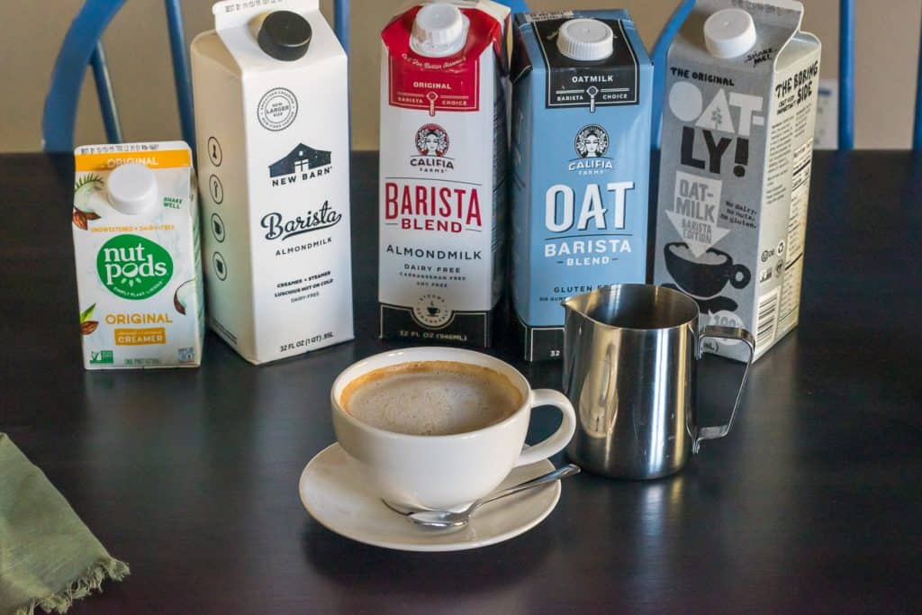 dairy free latte in small latte mug with a stainless steel pitcher and cartons of dairy free barista milk in the background including NutPods, The New Barn, Califia Farms,and Oatly