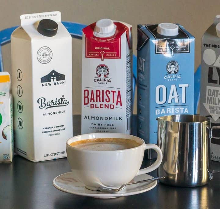 A white mug with a dairy free latte on a white saucer with a small silver spoon, and a metal milk frothing pitcher and cartons of dairy free and plant based barista milk in the background including NutPods, New Barn, Califia Farms, and Oatly