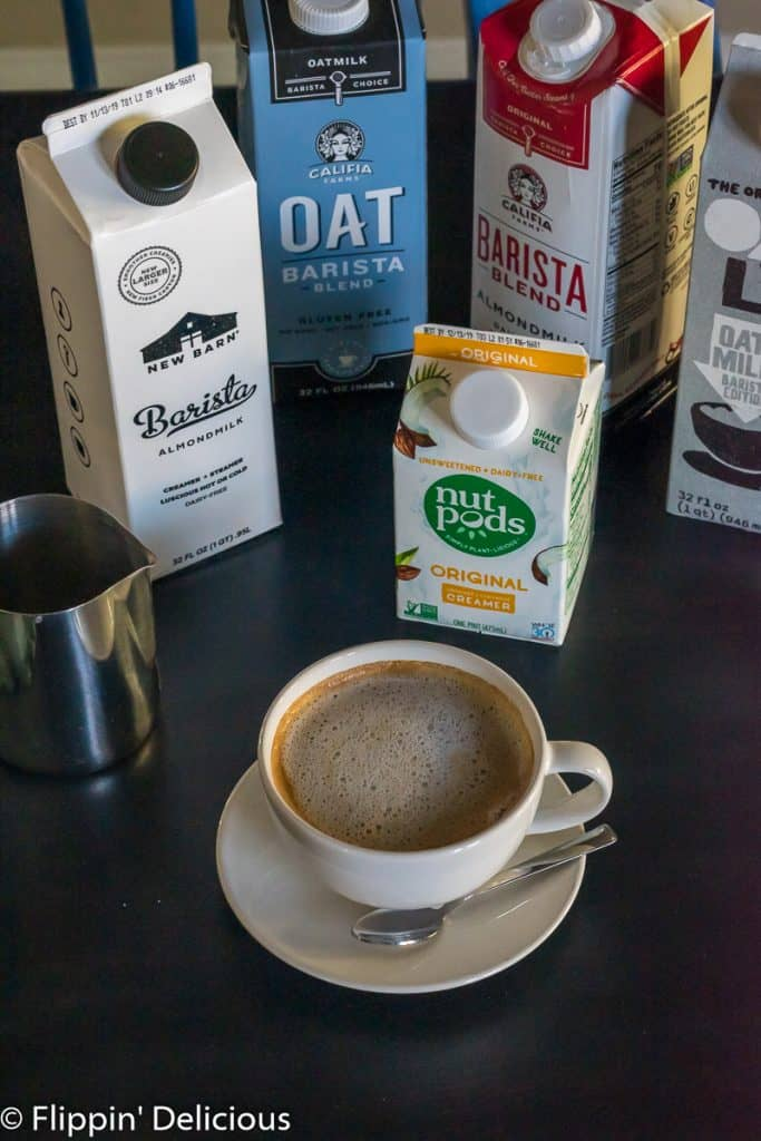 dairy free latte in small latte mug with a stainless steel pitcher and cartons of dairy free barista milk in the background