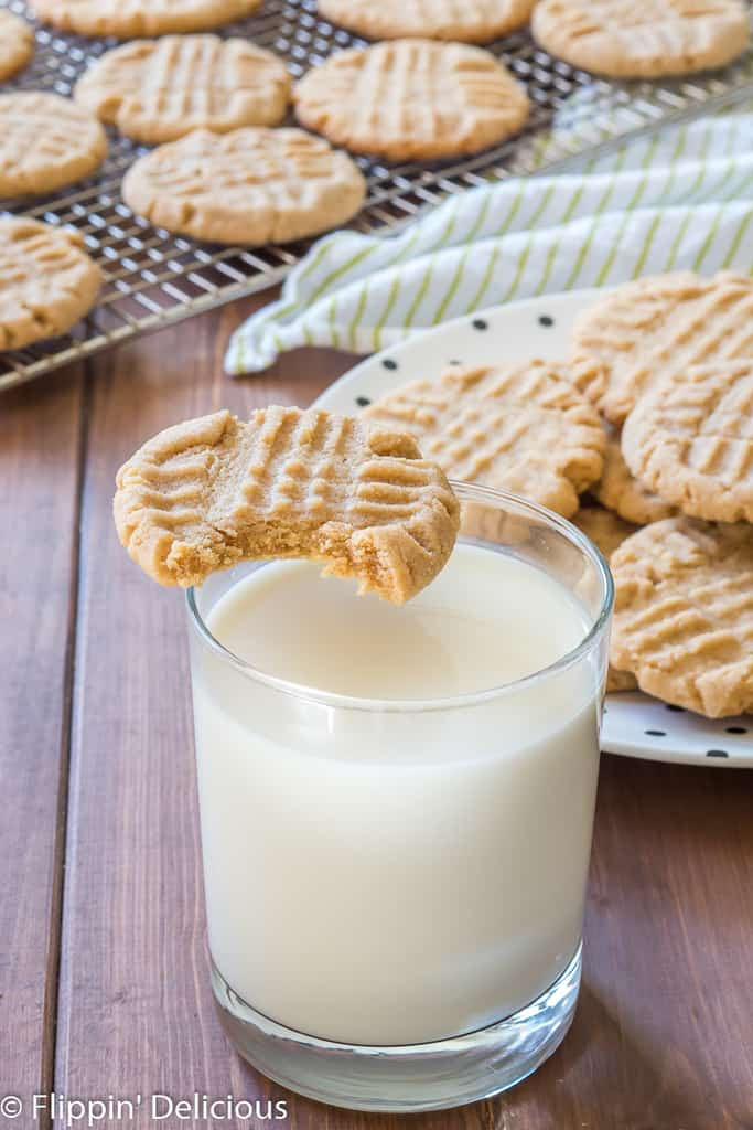 gluten free peanut butter cookie with bite taken out balanced on rim of glass of milk, with a plate full of gluten free peanut butter cookies in the background