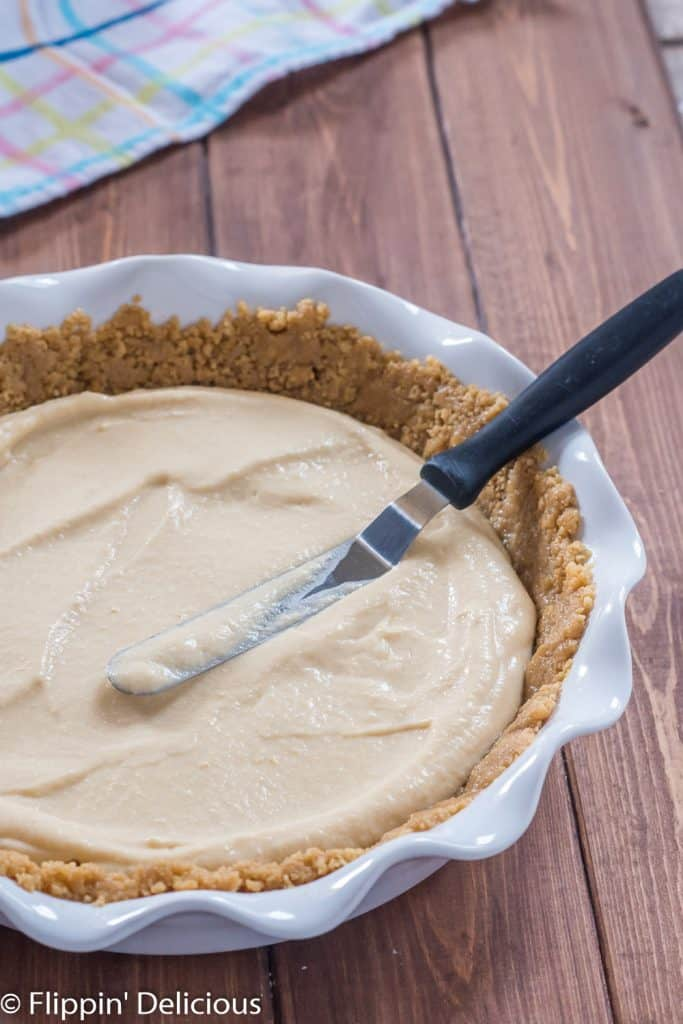 spreading vegan pudding into a pie crust ith an offset spatula