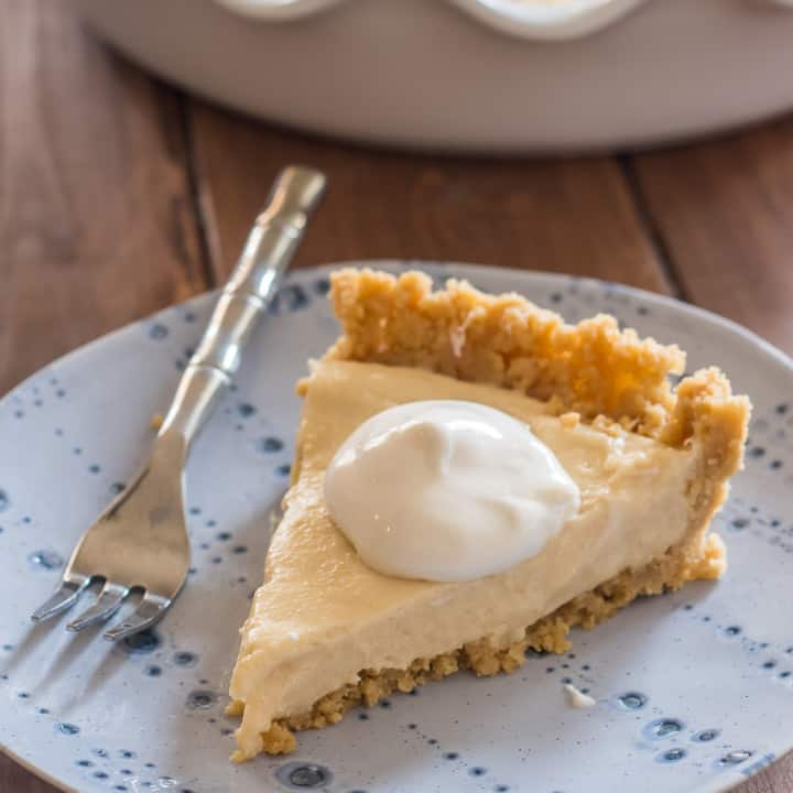slice of vegan pudding pie ith hipped topping on a blue plate with a small fork on a wooden table