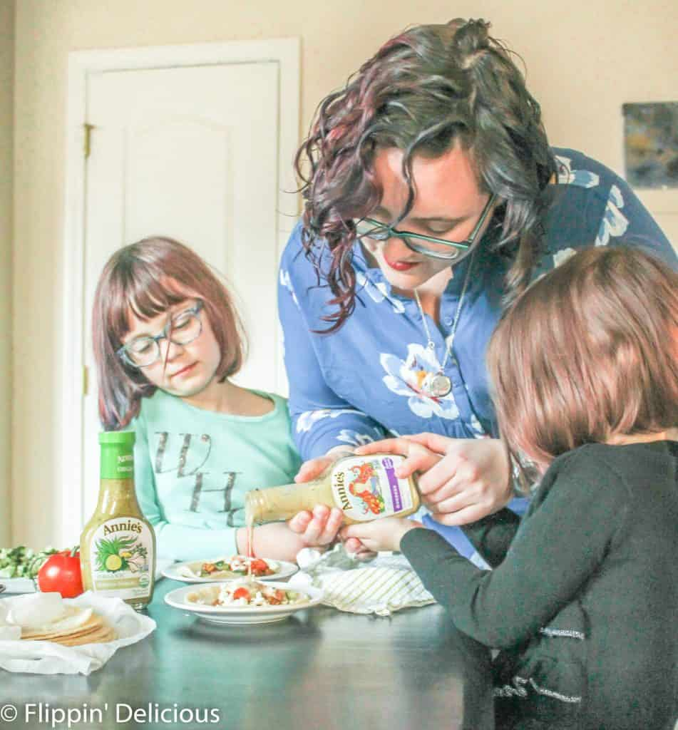 kids and mom pouring dressing on a greek vegetarian taco