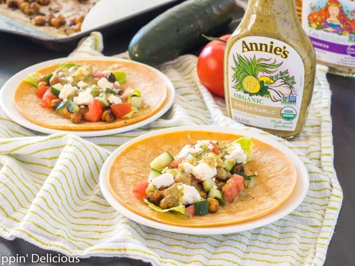 greek vegetarian tacos with chickpeas on a white plate with a green and white dish towel and bottle of annie's dressing
