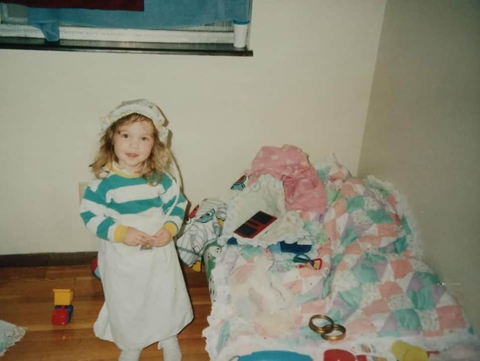 Brianna Fackrell Hobbs as a little girl pretending to cook with a doll dress on her head as a chef hat
