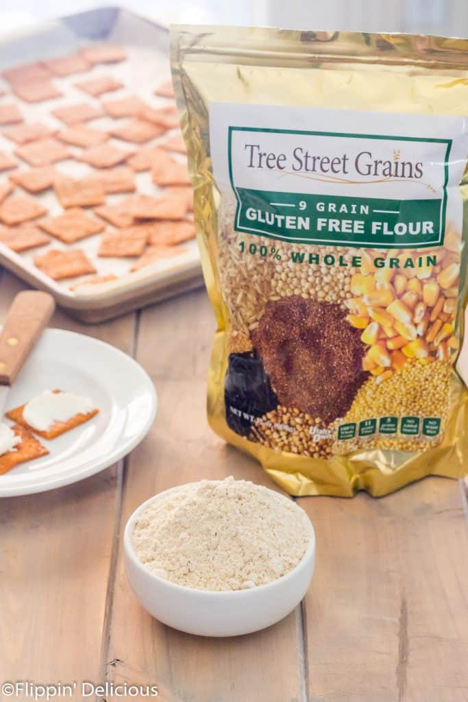 bag of tree street grains 9* grain gluten free flour on a wooden table beside a small bowl of gluten free flour with homemade gluten free pizza crackers in the background