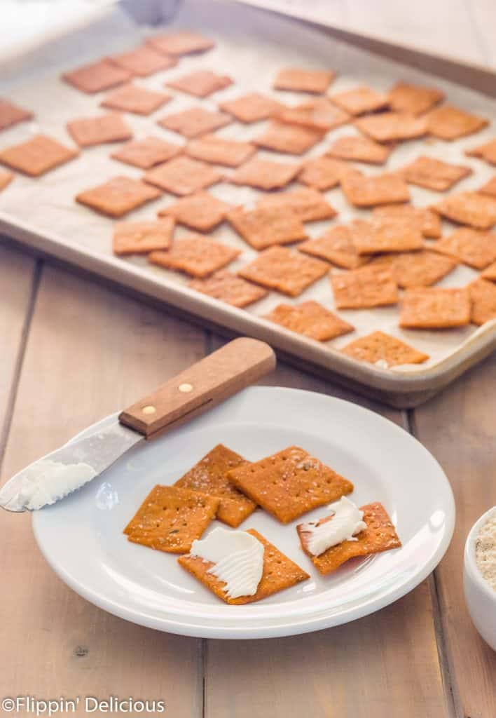 small white plate with five gluten free pizza crackers on it, two spread with cream cheese