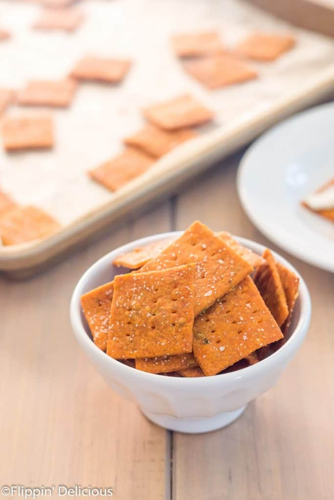 small white bowl filled with homemade gluten free pizza crackers on a wooden table with a pan of gluten free crackers in the background