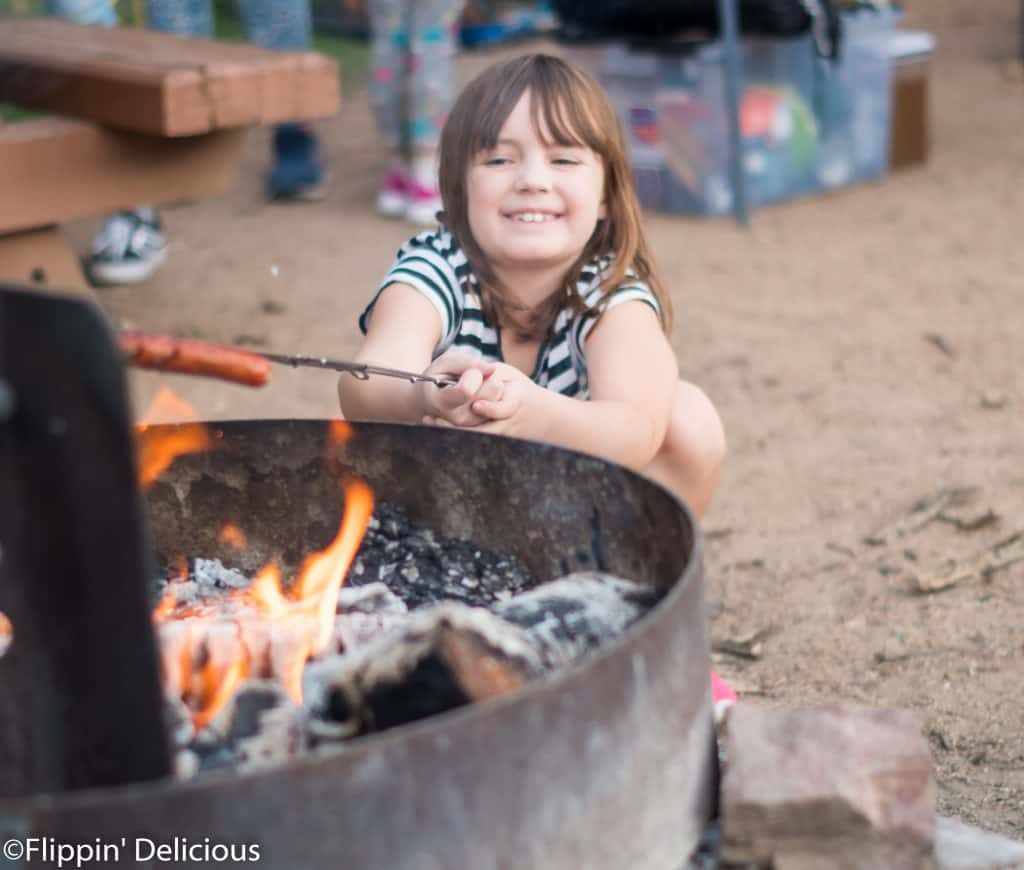 young girl roasting marshmallow over campfire