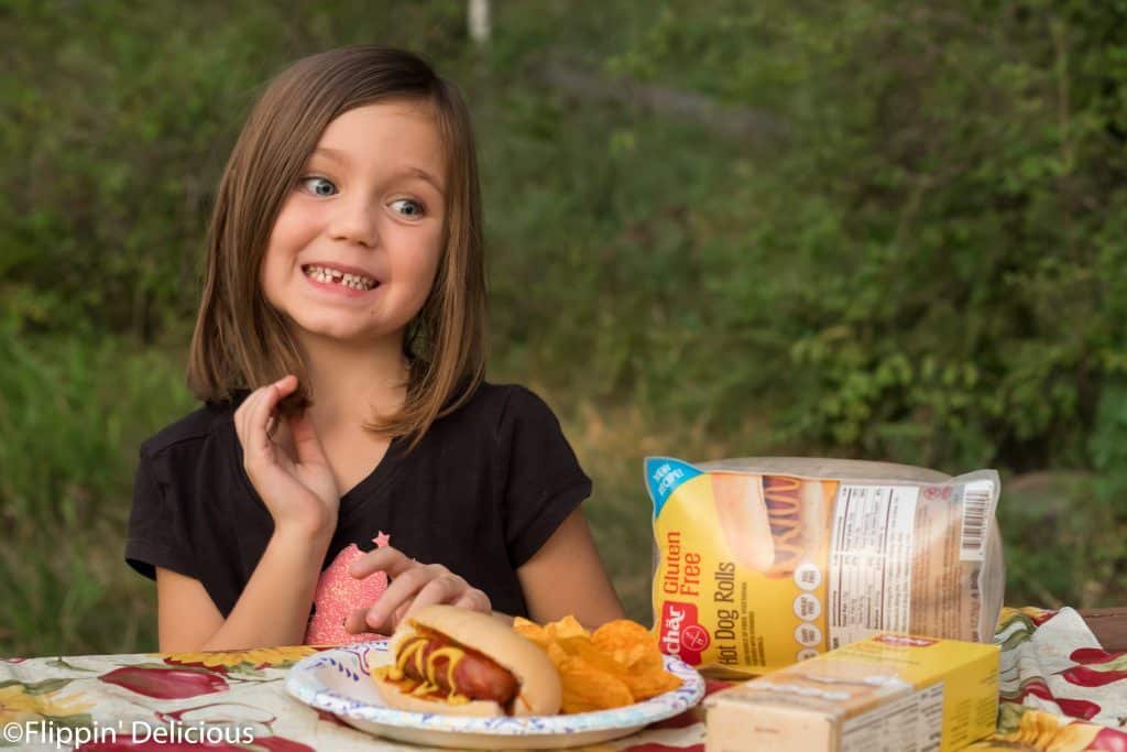 young girl with a gluten free hotdog and Schar's gluten free hot dog buns for gluten free camping food