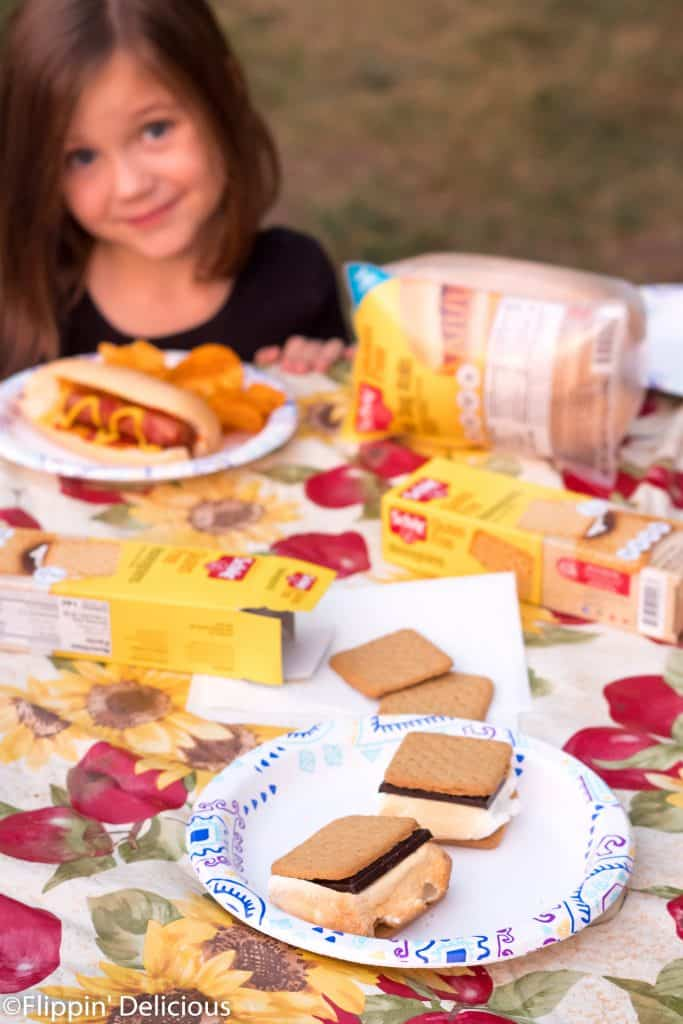 gluten free camping food including gluten free s'mores and gluten free hot dogs on a picnic table ith a young girl in the background