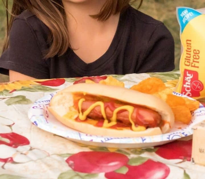 gluten free hot dog and package of gluten free schar hot dog buns and Honeygrams on a picnic table, young girl in the background