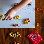 small hands arranging candy in number bonds