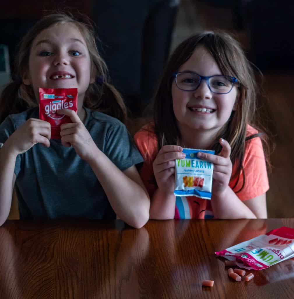two young girls holding YumEarth Organic candy, gummy bears and organic giggles