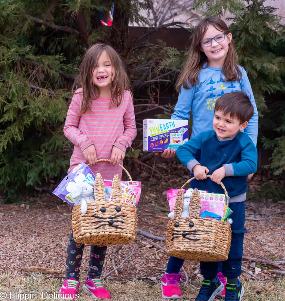 three kids holding easter baskets and yumearth fruit snacks