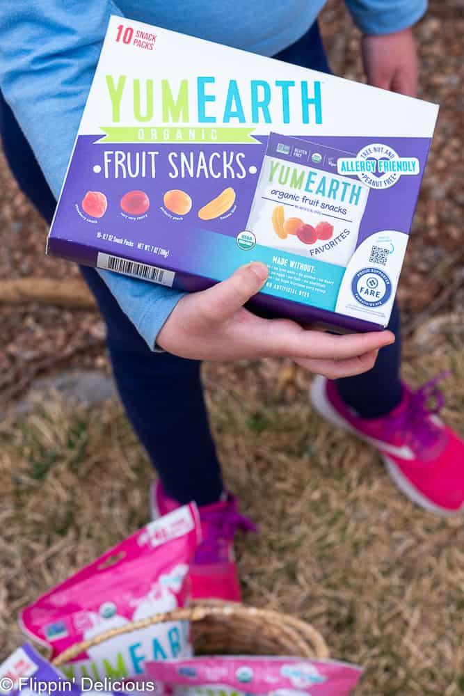 young girl holding yumearth fruit snacks
