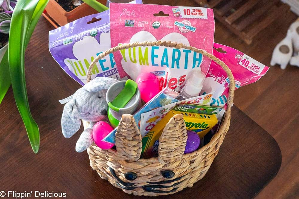inside of an allergy friendly easter basket with markers, water bottles, art supplies, stickers, stuffed bunny toy, and yumearth candy