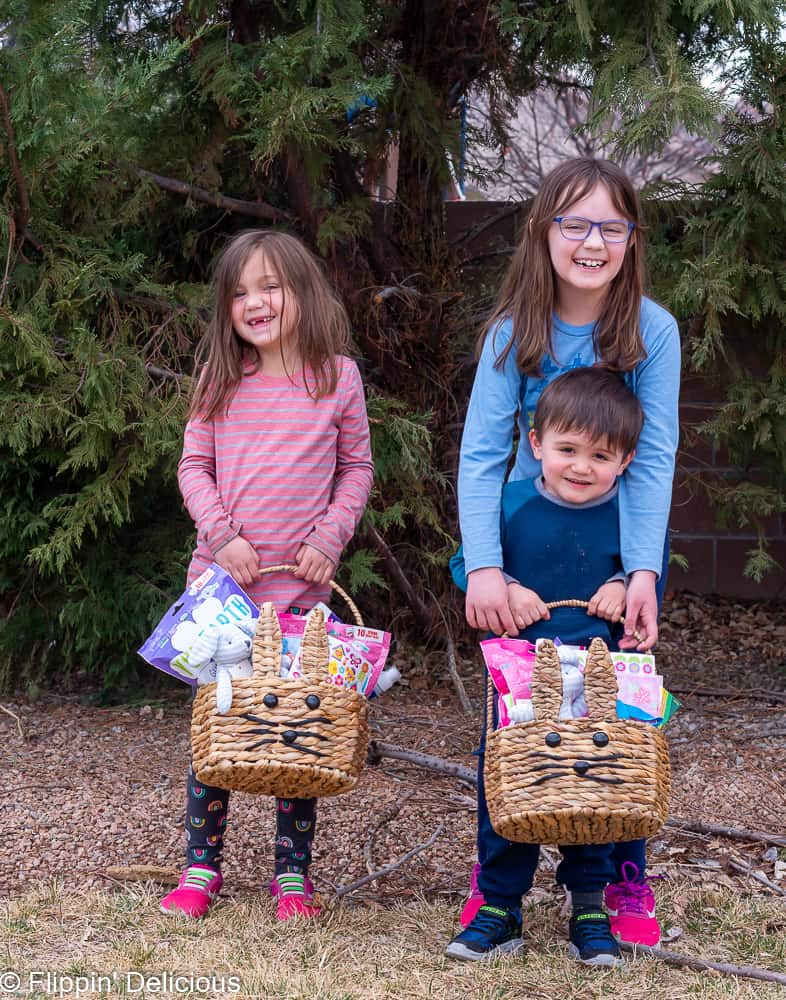 two young girls and a young boy holding two bunny easter baskets in front of a tree