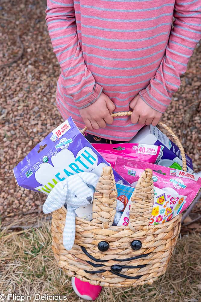 young girl holding allergy friendly easter basket with candy.
