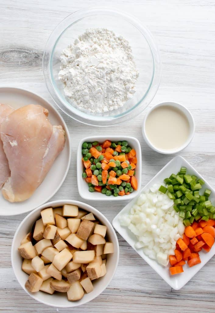 raw chicken, diced potatoes, choped carrots, chopped onion, chopped celery, frozen peas and carrots, egg and milk, all in small bows and dishes on a white background