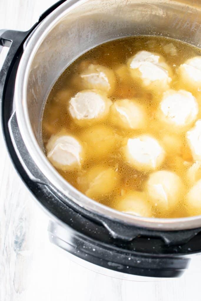 gluten free dumplings floating in chicken soup in an instant pot pressure cooker