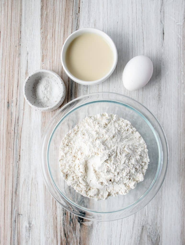 glass bowl with gluten free flour, an egg, white dish with baking powder an salt, and a white dish with dairy free milk