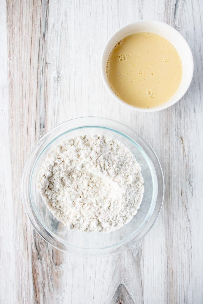 wet and dry ingredients for gluten free dumplings in bowls on a white wooden backdrop