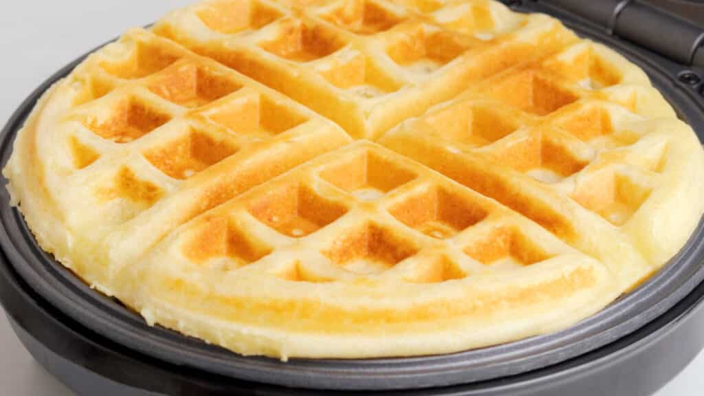 A gluten free waffle, golden brown, ready to come out of a belgian waffle iron