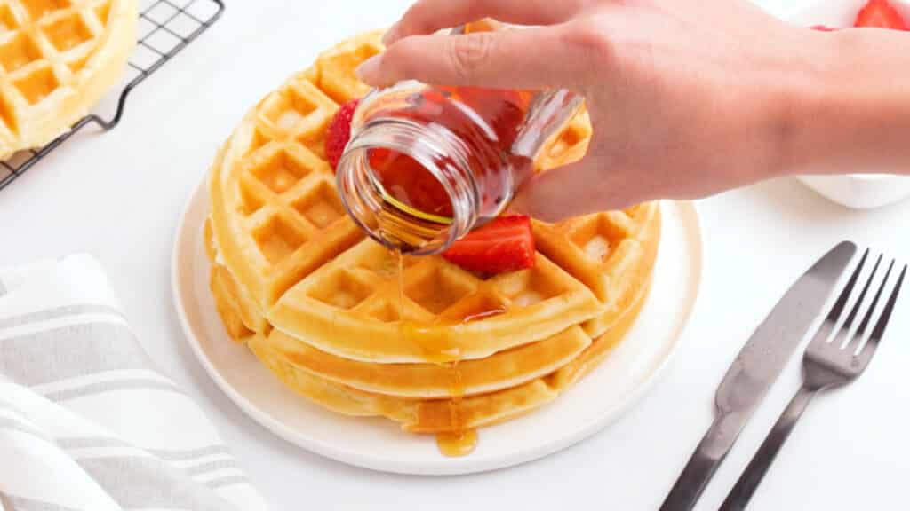 hand pouring syrup out of a glass jar over a stack of three gluten free waffles on a white plate, topped with strawberries.